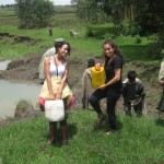 Morgan and Laura helping carry water from the local water source.